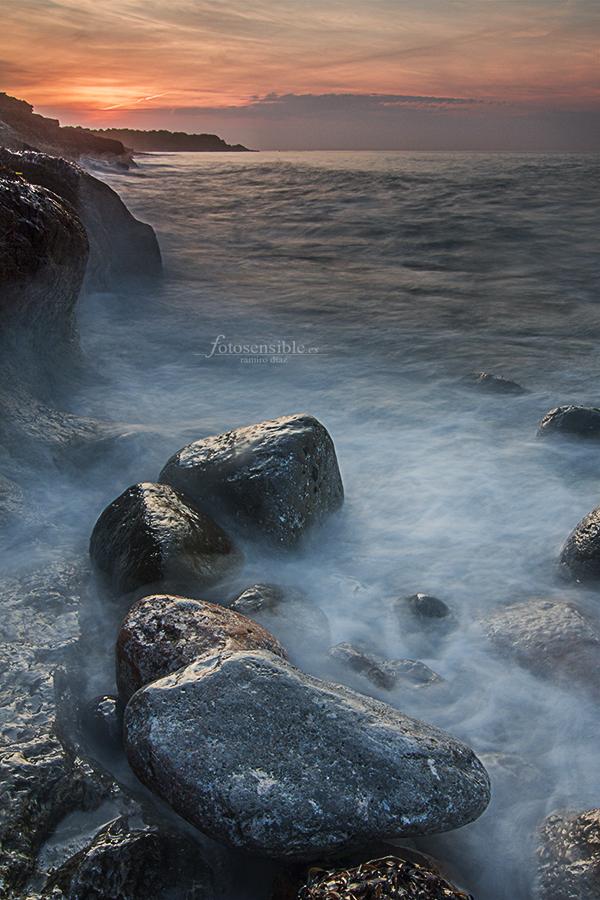 Luz del amanecer y bruma salada envuelven las rocas del acantilado mediterráneo.